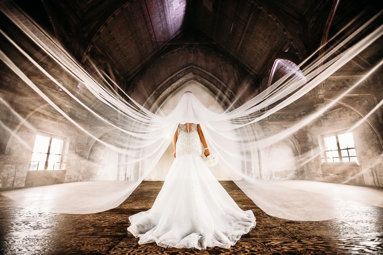 een foto van een bruid met een hele lange sluier in metaal kathedraal in utrecht