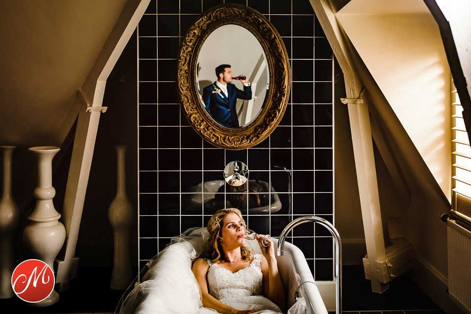 een bruid en een bruidegom op hun hotel kamer, de bruid ligt in bad met een flesje bier en de bruidegom staat er achter met een blikje cola in zijn hand