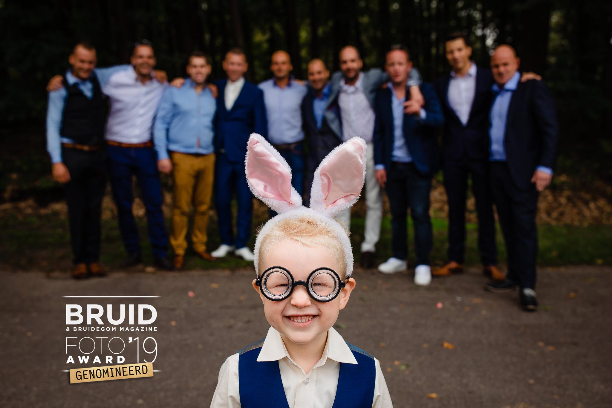 een groeps foto met op de voorgrond een heel schattig klein jongetje, hij draag een bril met soort jampot glazen en op zijn hoofd heeft hij een haarband met konijnen oortjes. een hilarische foto!