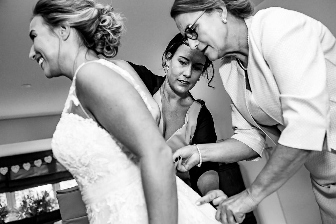 bruid word aangekleed door haar moeder en zus