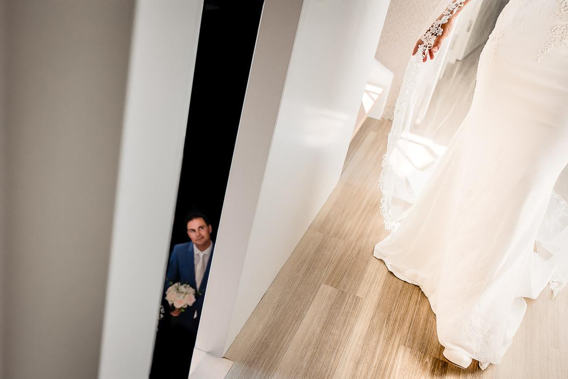 bruidegom staat onder aan de trap op zijn bruid te wachten