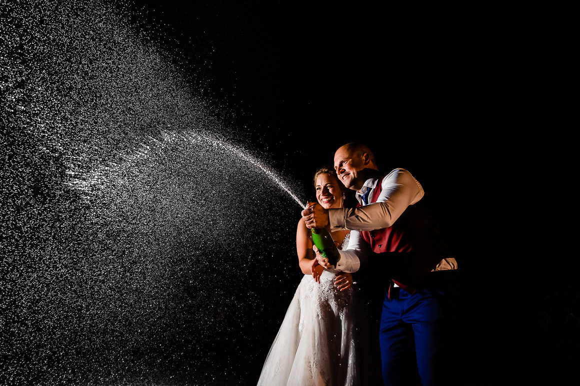 bruid en bruidegom spuiten met champagne