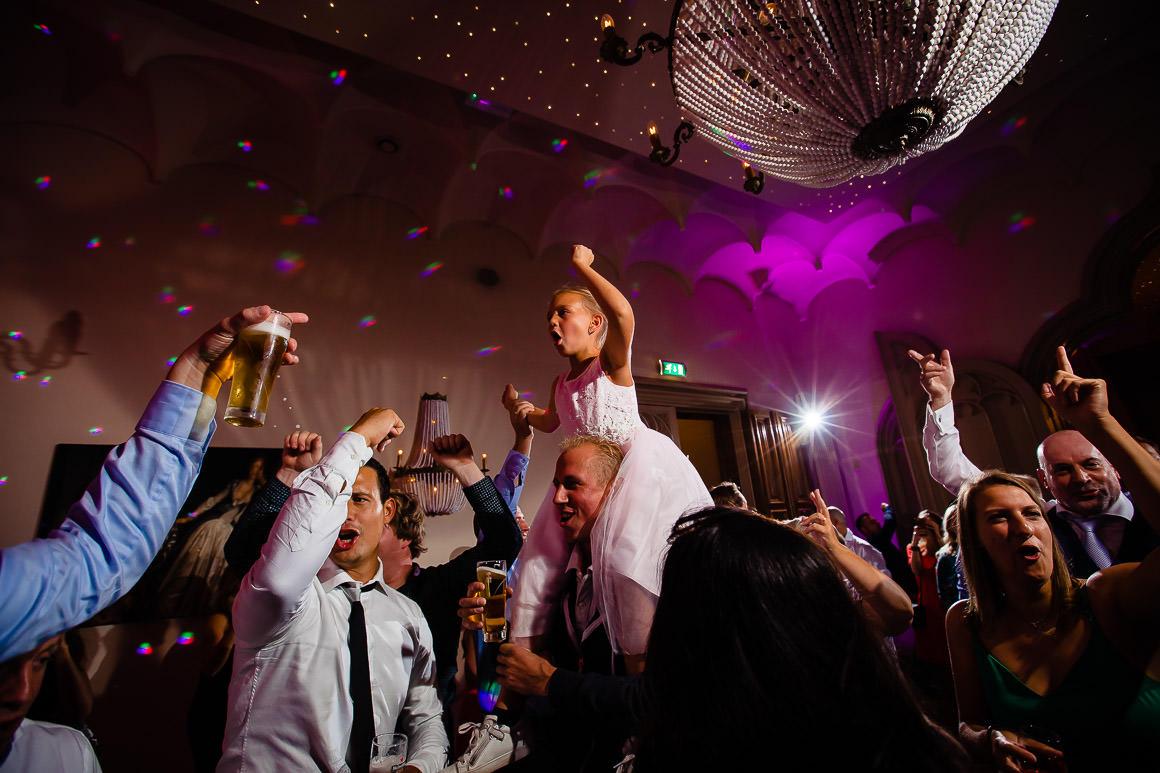 kleine nichtje van bruid en bruidegom wordt tijdens het feest opgetild door de gasten