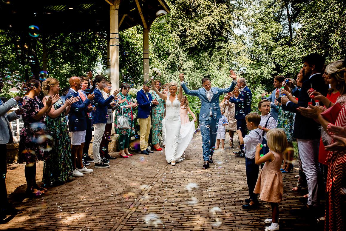 het bruidspaar loopt door een haag van mensen en belleblazen naar het terras na de ceremonie