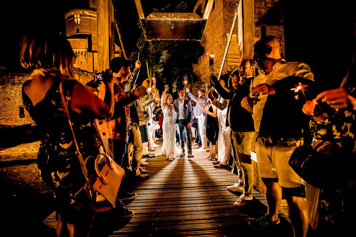 een foto waarbij het bruidspaar wordt uitgezwaaid door hun gasten met sterretjes in hun handen