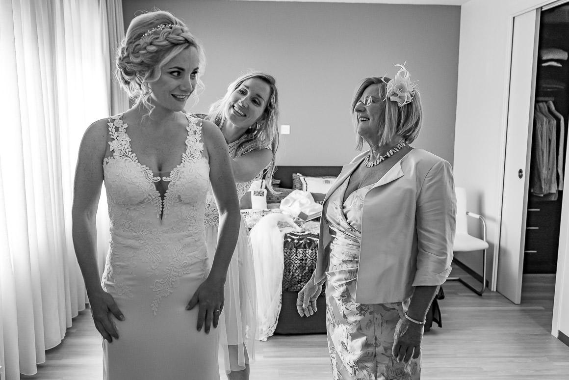 de bruid wordt aangekleed door haar zus en moeder