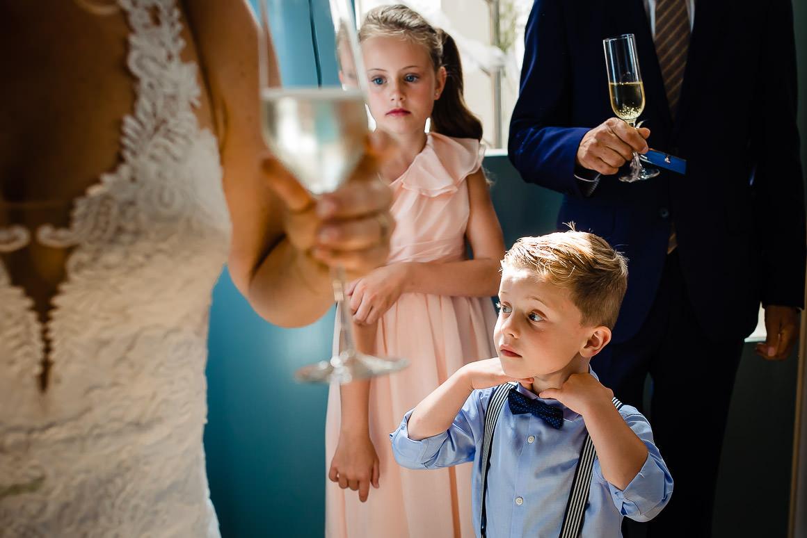 een foto van het zoontje van het bruidspaar wat zijn strikje goed doet