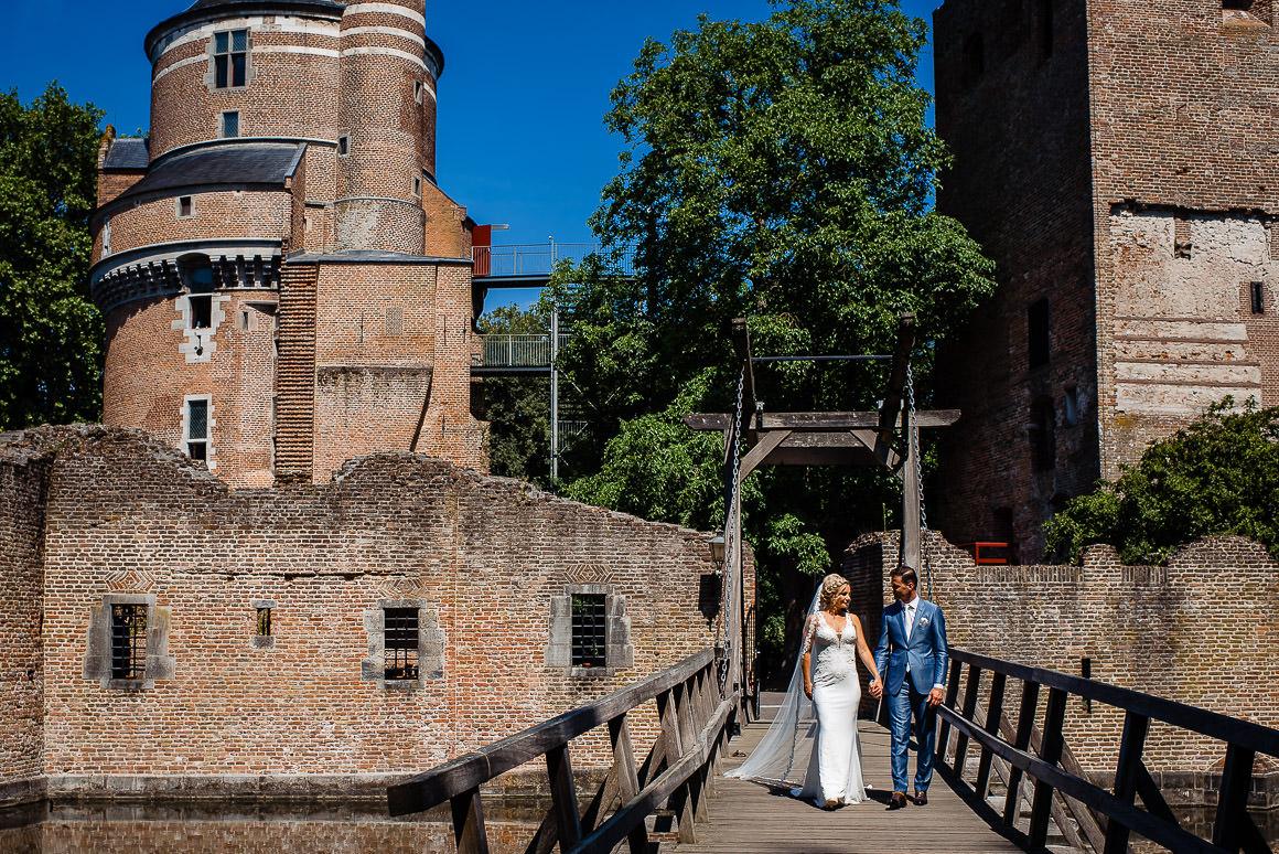 bruid en bruidegom lopen over de brug van het kasteel