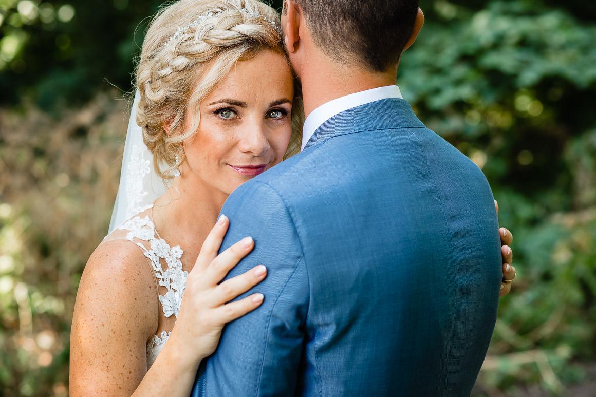 een close up van de bruid die met haar hoofd op de schouders van de bruidegom rust