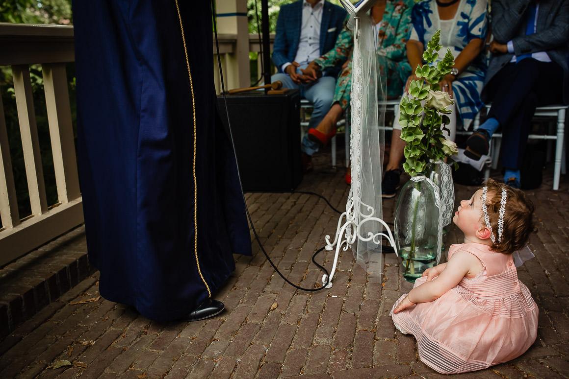 kindje van het bruidspaar zit aandachtig te luisteren naar de trouwambtenaar