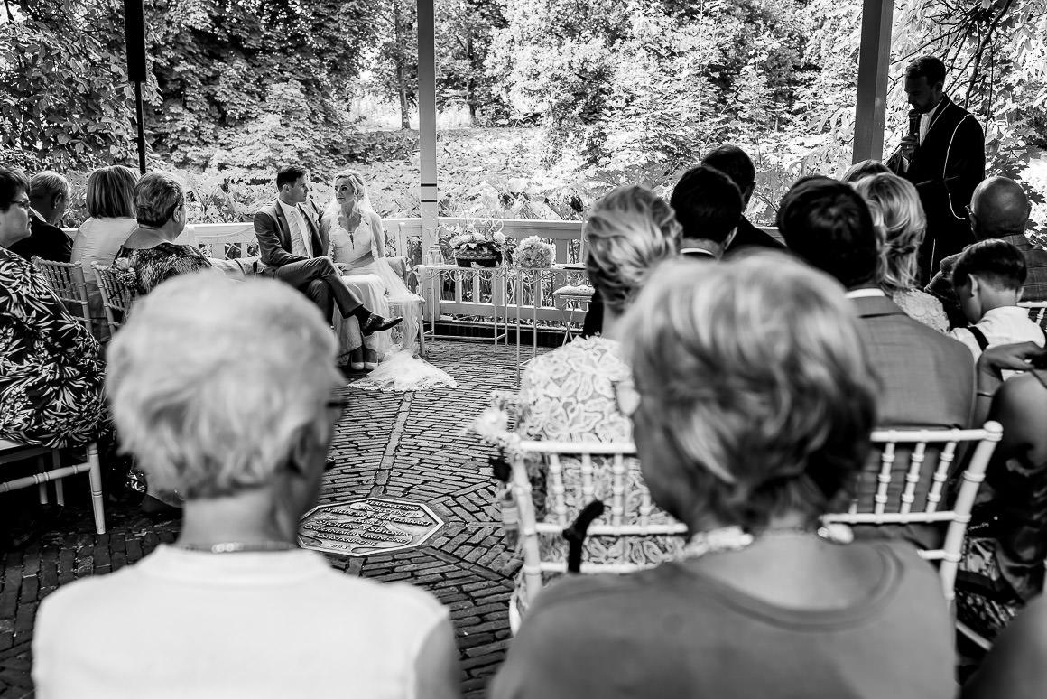 een overzicht foto van de buiten ceremonie met het bruidspaar in het midden